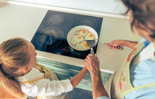 Niña y su padre en delantales están cocinando huevos fritos.