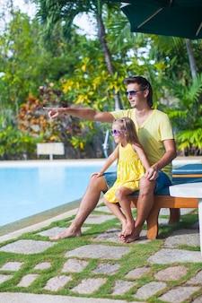 Niña con su padre divertirse cerca de la piscina en el exótico resort