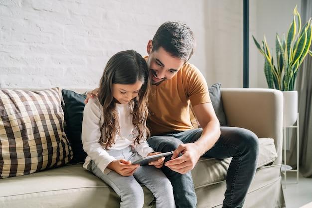 Niña y su padre se divierten juntos mientras juegan con una tableta digital en casa. concepto de familia monoparental.