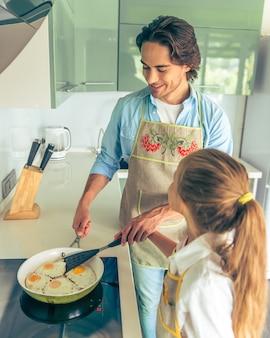 Niña y su padre guapo están cocinando huevos fritos.