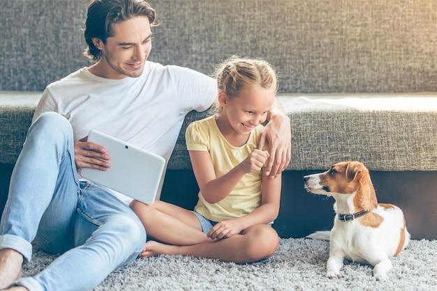 Niña y su padre guapo están jugando con su perro.