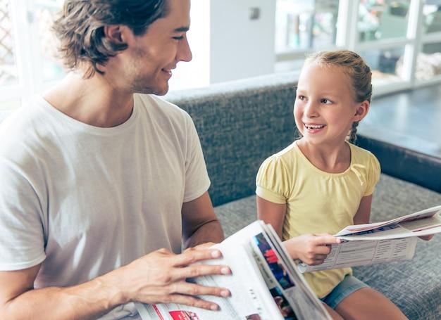 Niña y su padre guapo están leyendo periódicos.