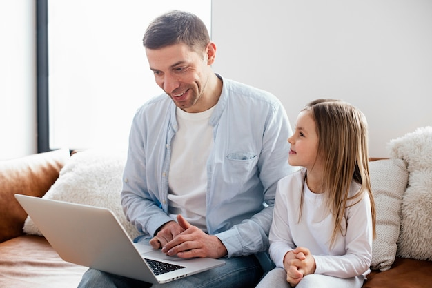 Niña y su padre pasan tiempo en la computadora portátil
