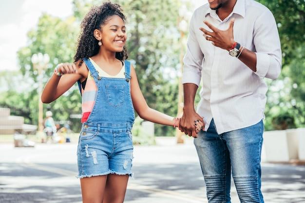 Niña con su padre pasar un buen rato juntos en un paseo al aire libre en la calle
