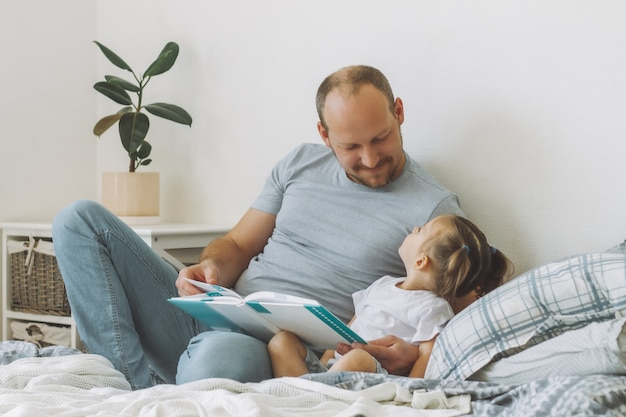 Niña con su padre se sienta en la cama en la habitación y lee el libro