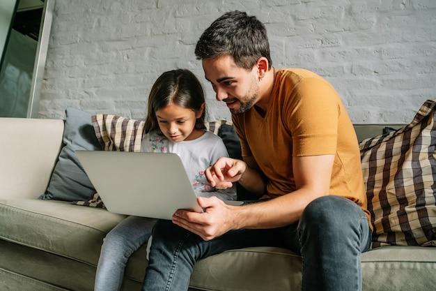 Niña y su padre usando una computadora portátil juntos en casa.