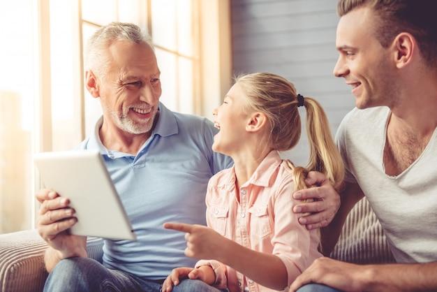 Niña, su papá y su abuelo están usando tableta digital