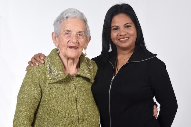 Niña sudamericana cuidando a una anciana sobre pared blanca
