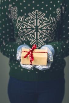 Una niña en un suéter de año nuevo tiene un regalo. regalos para hombres. feliz navidad. regalo para una niña. suéter con adornos navideños. vestido de punto.