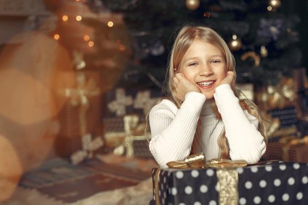 Niña en un suéter blanco cerca del árbol de navidad con presente