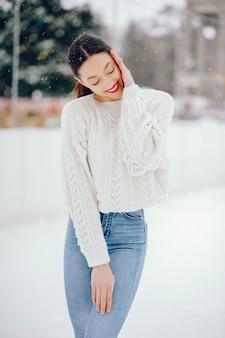 Niña en un suéter blanco de pie en un parque de invierno