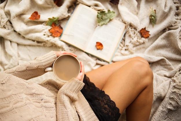 Una niña en un suéter caliente se sienta en una manta de lana beige y sostiene una taza de café caliente en sus manos.
