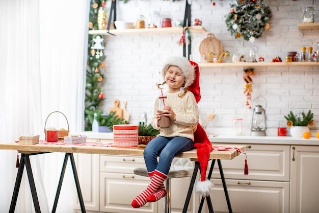 Una niña con un suéter y un gorro de papá noel, bebiendo leche de cacao sentada en la mesa de la cocina.