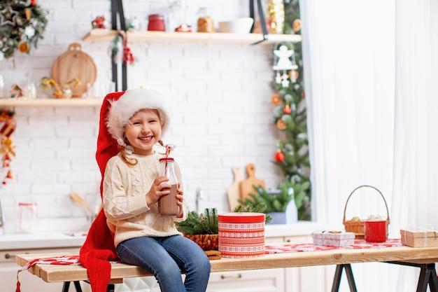 Una niña con un suéter y un gorro de papá noel.