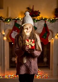 Niña en suéter de lana y sombrero mirando dentro de la caja presente brillante