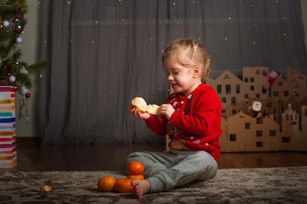 Niña con un suéter rojo con un ciervo para el año nuevo. una niña y mandarinas en el árbol de navidad.