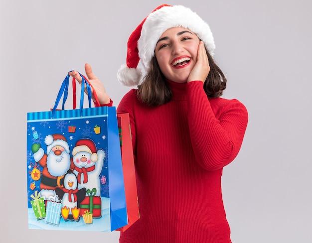 Niña de suéter rojo y gorro de papá noel con bolsas de papel de colores con regalos de navidad mirando a la cámara con cara feliz de pie sobre fondo blanco.