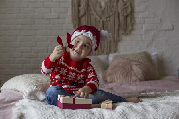 Niña en un suéter rojo rojo de navidad y gorro de papá noel juega en la cama con regalos