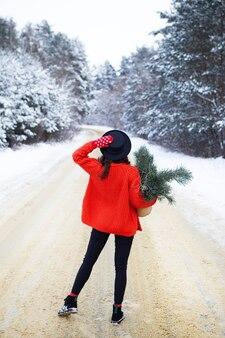 Una niña con un suéter rojo y un sombrero se encuentra en medio de un camino nevado en un bosque con ramas de pino. viaje de fin de semana.