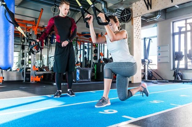 La niña bajo la supervisión de un instructor hace ejercicios de estocadas en los bucles trx. foto horizontal