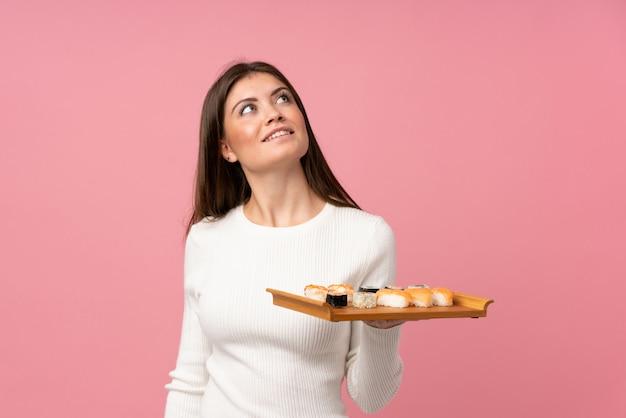 Niña con sushi sobre pared rosa aislado mirando hacia arriba mientras sonríe
