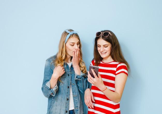 Una niña susurra algo al oído de su novia mirando su teléfono celular