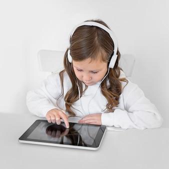 Niña con tableta con auriculares