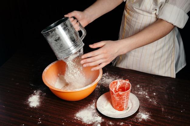 La niña tamiza la harina en un tamiz de acero.