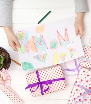 Niña con tarjeta de artesanía para el día de celebración de la madre feliz