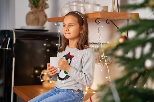 Una niña con una taza de té caliente en navidad