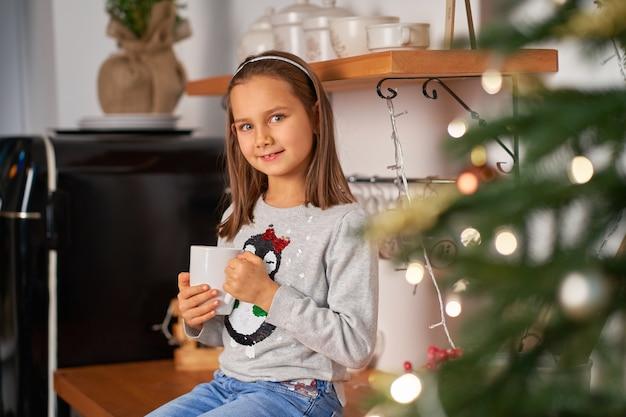 Una niña con una taza de té caliente sueña con un regalo de papá noel para navidad.
