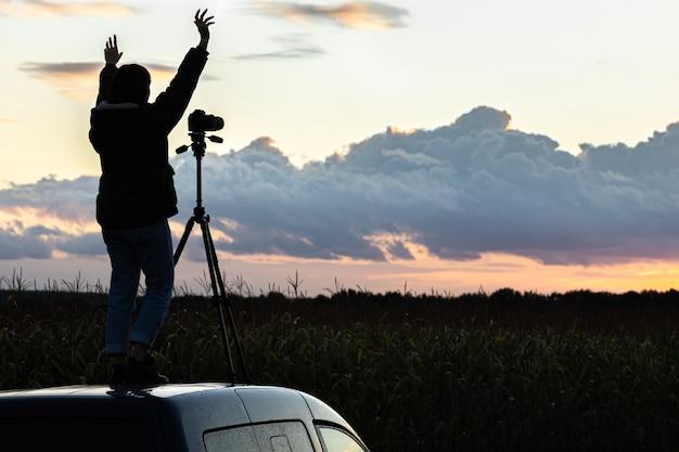 La niña en el techo del auto fotografía la puesta de sol con un trípode