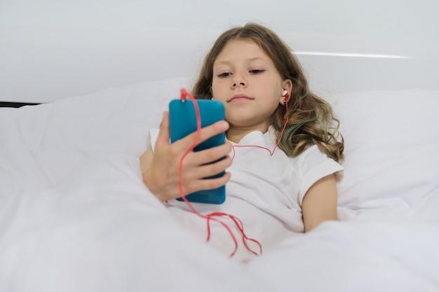 Niña con teléfono móvil en auriculares, sentado en la cama blanca de casa