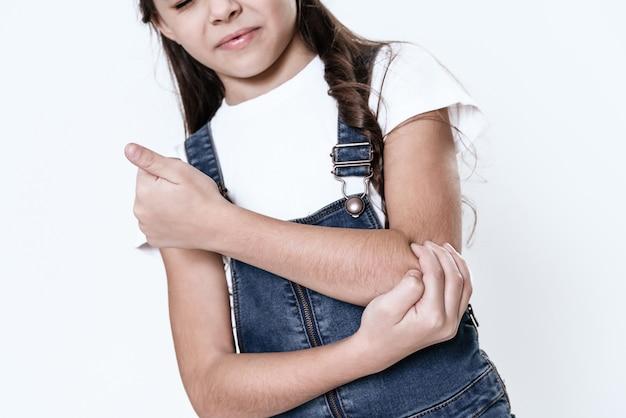 La niña tiene un dolor en el brazo en la habitación blanca.