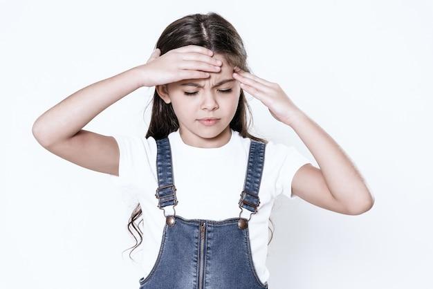 La niña tiene un dolor de cabeza. él lleva su mano a su cabeza.