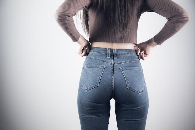 Niña tira de jeans sobre un fondo gris