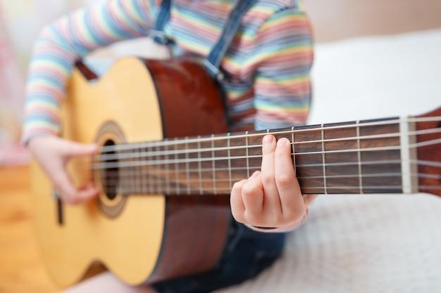 Niña toca la guitarra en casa.