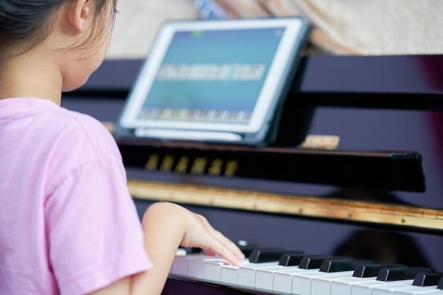 Niña toca las teclas del piano en casa