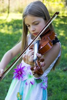Niña toca el violín afuera