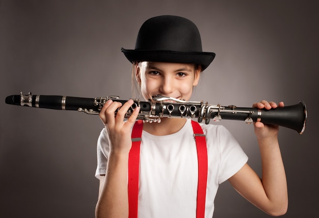 Niña tocando el clarinete sobre un fondo gris