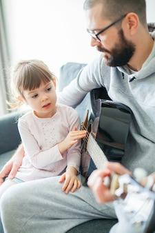 Niña tocando cuerdas de guitarra mientras su padre toca la guitarra para ella