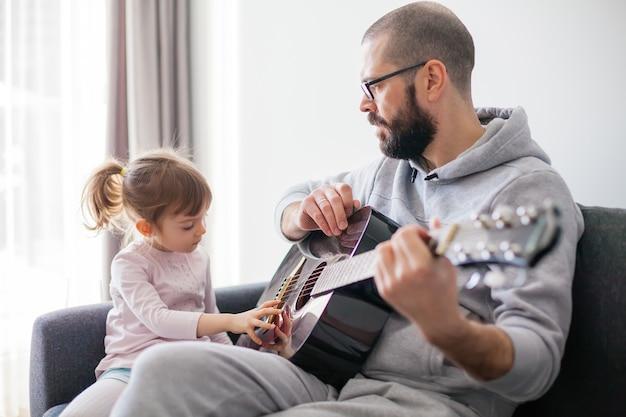 Niña tocando las cuerdas de la guitarra. su padre le está enseñando a tocar la guitarra.