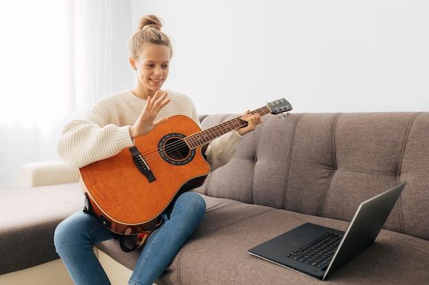 Niña tocando una guitarra en casa