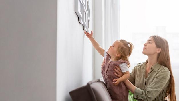 Niña tocando el marco en la pared
