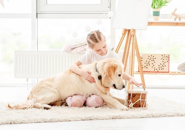 Niña tocando música con perro