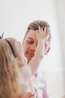 Niña tocando el pelo de su padre