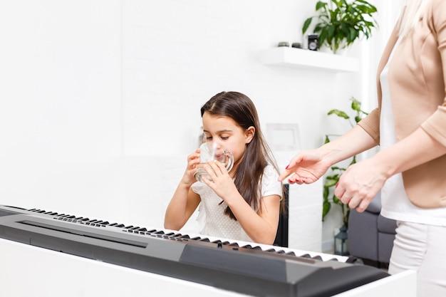 Niña tocando el piano en casa, aprendiendo en línea