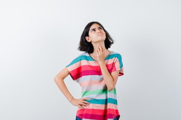 Niña tocando la piel de su cuello en camiseta y mirando pensativa. vista frontal.