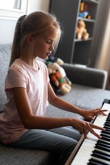Niña tocando el teclado en casa