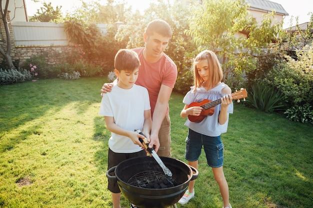 Niña tocando el ukelele de pie cerca de su padre y su hermano cocinando comida en una barbacoa